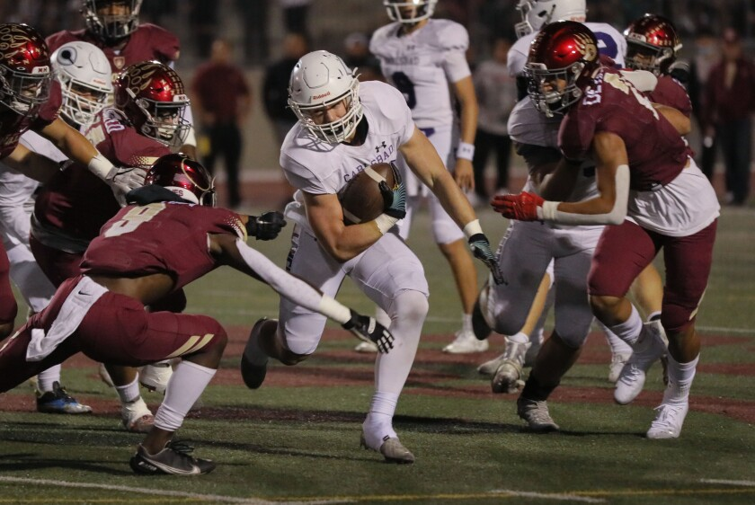 Carlsbad's Anthony Ferrelli tries to get around Mission Hills' Carmelo Chapman in Carlsbad's 13-7 win Friday night.