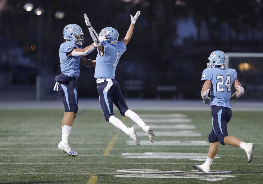 Corona del Mar's Max Lane (1) jumps into the arms of teammate Tommy Griffin (3) after scoring a touchdown on Friday.
