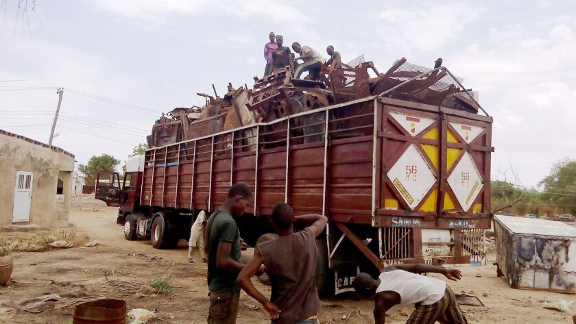 Residents evacuate in a truck full of metal sheets collected from houses burned after Boko Haram attacks in Buni Yadi on May 21, 2016.