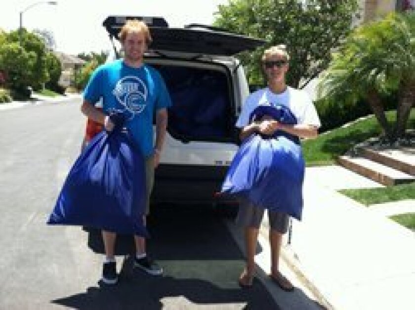 Teen Volunteers In Action members Billy Tifft and Stephen Tifft display the 31 personalized duffle bags that are filled with many wonderful items and were created by TVIA volunteers for the 31 foster teens who are graduating from San Pasqual Academy.