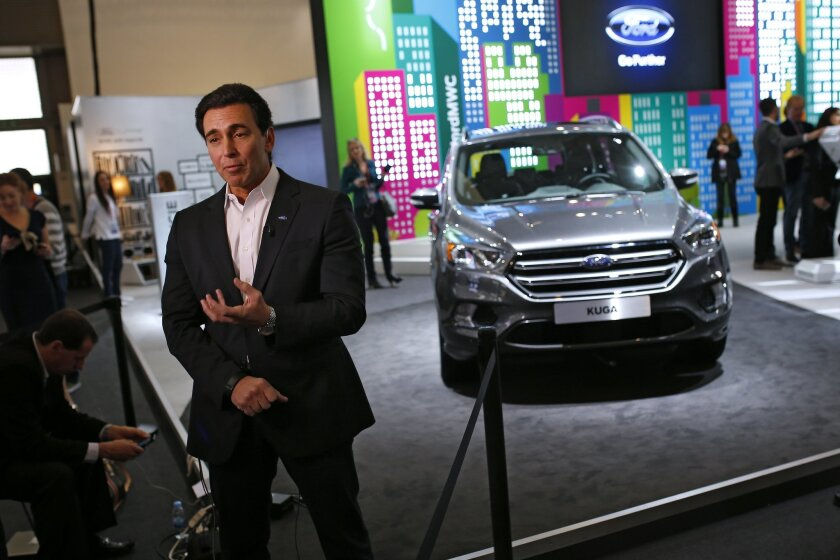 Ford CEO Mark Fields talks during an interview next to the new Kuga SUV car, which features its latest connectivity and driver-assisted technology, during the Mobile World Congress Wireless show, the world's largest mobile phone trade show, in Barcelona, Spain, Monday, Feb. 22, 2016. (AP Photo/Francisco Seco)