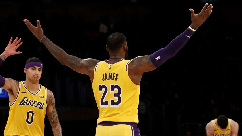 Lakers Kyle Kuzma, left, LeBron James and Lonzo Ball celebrate a basket made by James against the Pacers late in the fourth quarter.