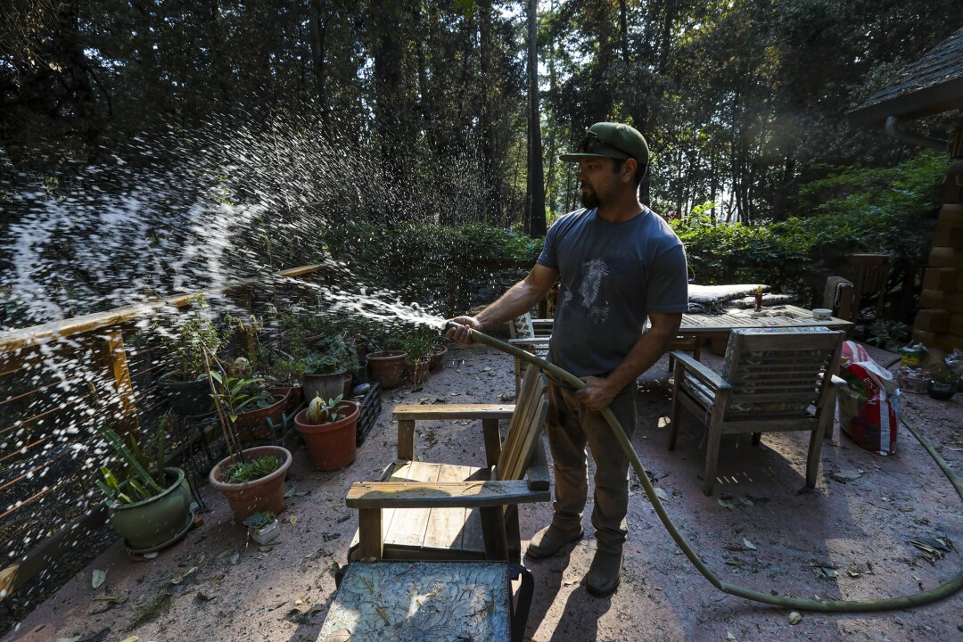 Jonah Torres, a cannabis dealer, waters plants on the terrace of an evacuated neighbor.