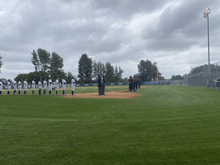 Birmingham and JSerra players stand for the national anthem on a cloudy Tuesday in Lake Balboa.