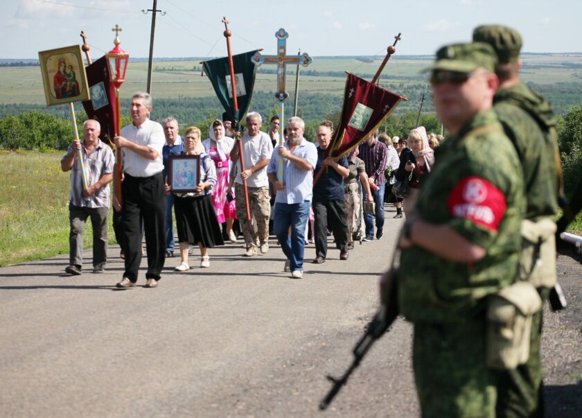 About 200 Ukrainian villagers marched near Grabove on Friday in memory of those killed a year earlier when Malaysia Airlines Flight 17 was shot down over the separatist-held farming town in eastern Ukraine.