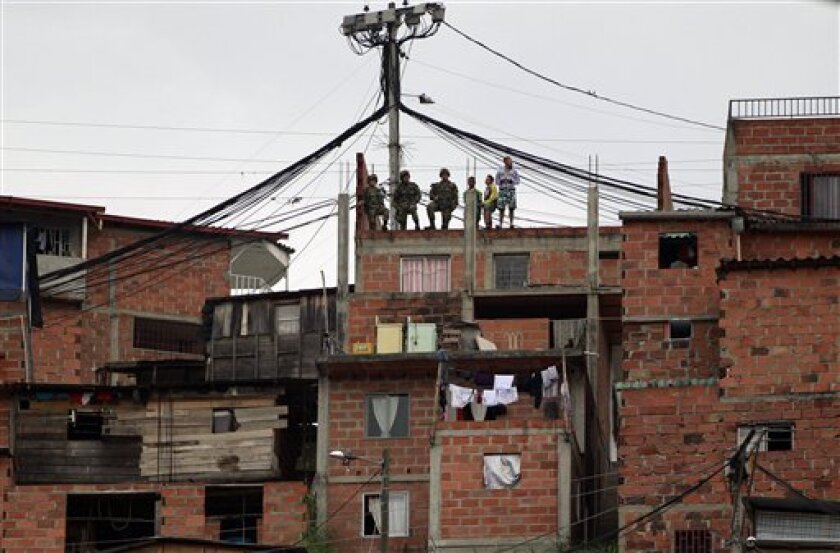 Soldiers stand on the roof of a home during routine patrols in Medellin, Colombia, Wednesday Sept. 1, 2010. (AP Photo/Fernando Vergara)