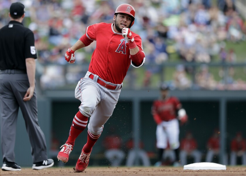 Angels' David Fletcher races toward third base before being sent back on what was ruled a ground rule double against the Arizona Diamondbacks in the third inning of a spring training game on Thursday in Scottsdale, Ariz.