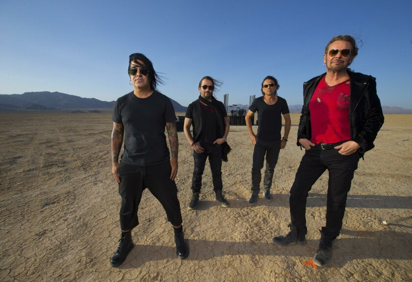 """From left: Mana drummer Alex Gonzalez, guitarist Sergio Vallín, bassist Juan Calleros, singer Fher Olvero, pose for a portrait in the middle of Lucerne Lake dry lake bed, Mojave Desert, while making a video for their song """"la prisi—n"""" May 6, 2015. (Photo By Allen J. Schaben / Los Angeles Times)"""