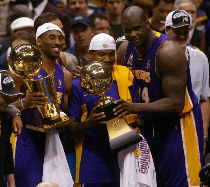 Lakers' Kobe Bryant holds up the Larry O'Brien Trophy as Lindsey Hunter and Shaquille O'Neal hold the MVP Trophy.