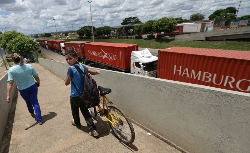 A boy walks his bicycle down a pedestrian ramp that crosses a federal highway where striking truckers have parked their trucks in Goiania, Brazil, Wednesday, Feb. 25, 2015. Weeklong protests by Brazilian truckers demanding lower fuel and toll prices have spread, causing shortages of gasoline and other products. They are also protesting low freight prices and demanding freight costs be based on the distances trucks travel to deliver goods, not by tonnage. (AP Photo/Eraldo Peres)