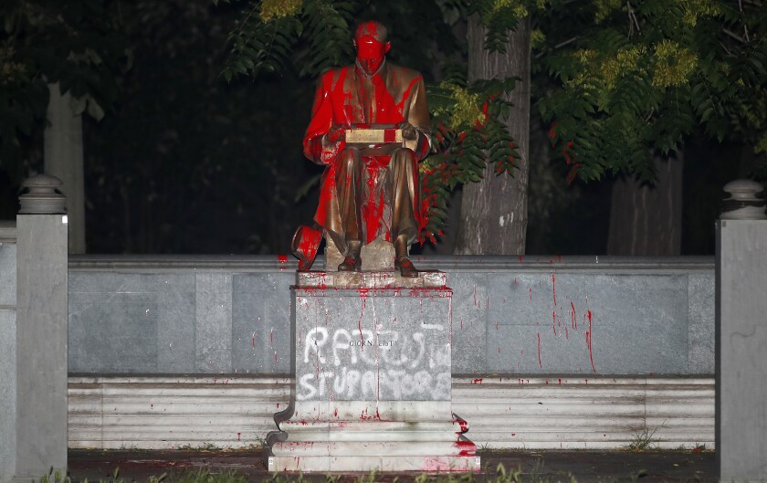"CORRECTS CIRCUMSTANCES IN WHICH STATUE WAS VANDALIZED. Red paint and words in Italian reading ''racist"", above, and ""rapist'' are seen on a statue of late Italian journalist Indro Montanelli, who had acknowledged having had a 12-year-old Eritrean bride while stationed in the Italian colony in the 1930s, in a Milan park that bears his name, northern Italy, late Saturday, June 13, 2020. The statue of Montanelli has been a flashpoint in Italy's Black Lives Matters protests, which have put renewed focus on Italy's colonial past. (AP Photo/Antonio Calanni)"
