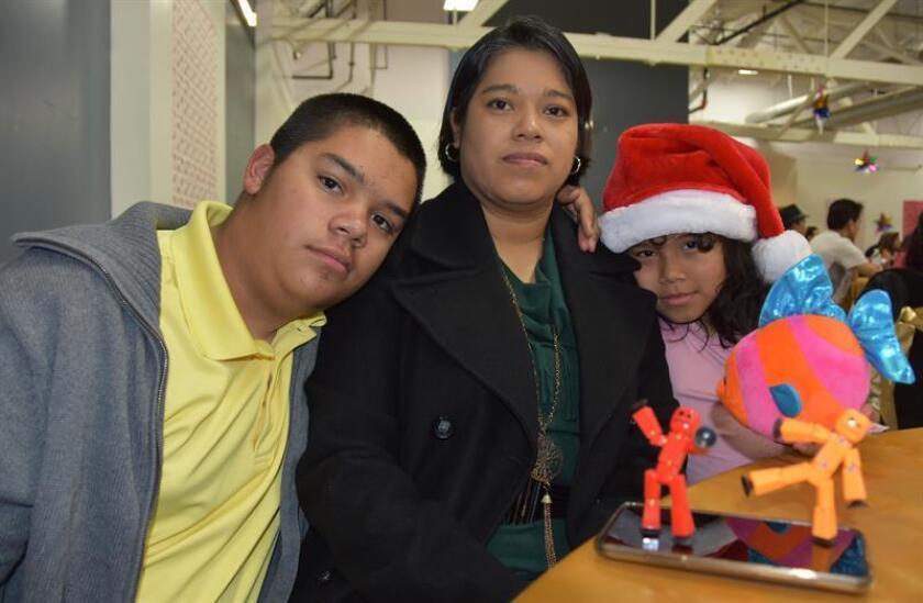 La salvadoreña beneficiaria del Estatus de Protección Temporal (TPS), Verónica Lagunas (c), y sus hijos Alexandre y Lydia, ambos estadounidenses, participan en la fiesta de navidad del Sindicato Internacional de Empleados de Servicios (SEIU) celebrada este domingo, 17 de diciembre de 2017, en Los Ángeles, California (EE.UU). EFE