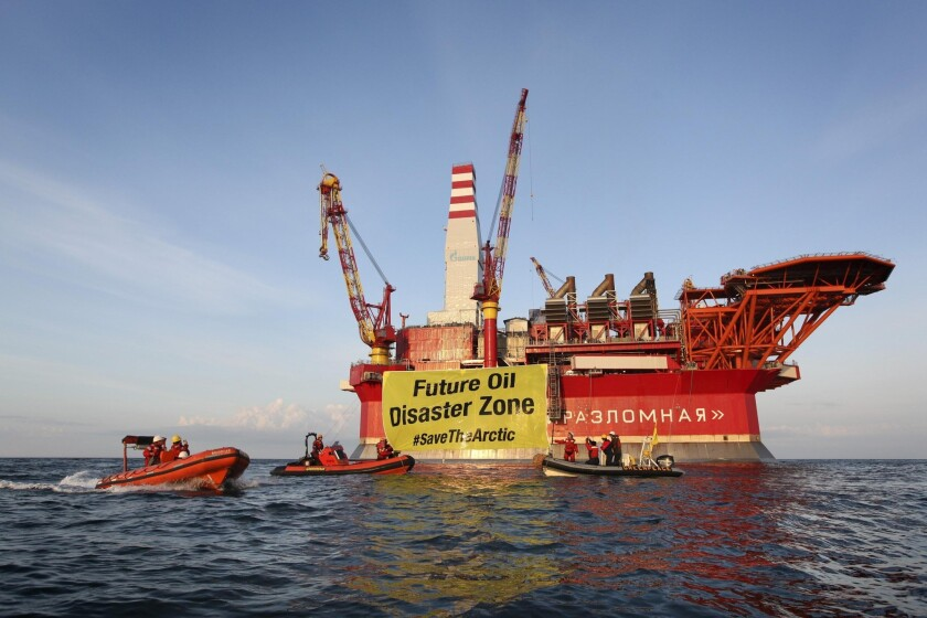 In this Aug. 25, 2012, file photo provided by Greenpeace, a banner unfurled by activists who scaled the Gazprom Prirazlomnaya oil-drilling platform in the Barents Sea warns of environmental disaster from exploitation of Arctic resources.