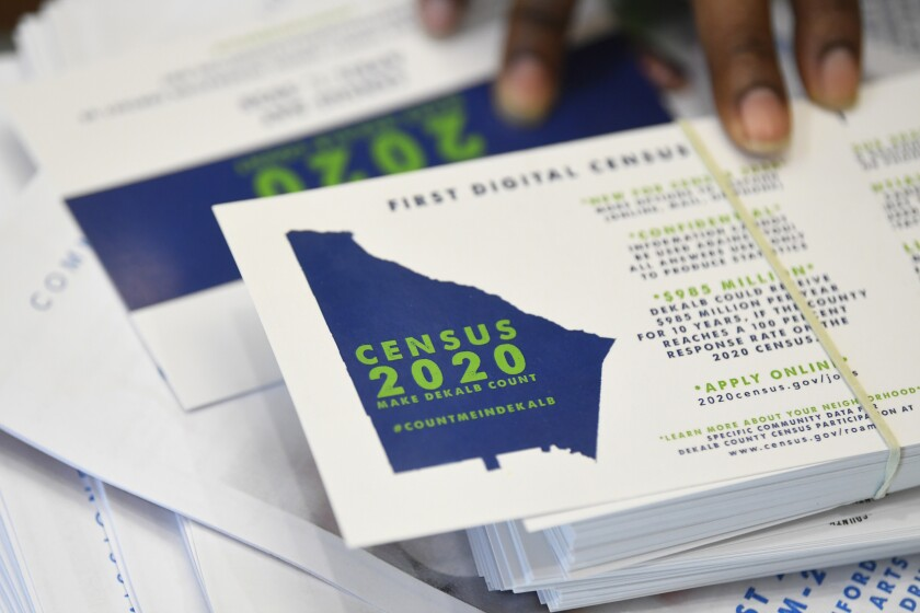 FILE - In this Aug. 13, 2019, file photo, a worker gets ready to pass out instructions on how to fill out the 2020 census during a town hall meeting in Lithonia, Ga. Because of the new coronavirus, the U.S. Census Bureau has postponed sending out census takers to count college students in off-campus housing and delayed sending workers to grocery stores and houses of worship where they help people fill out the once-a-decade questionnaire. The Census Bureau said in a statement Sunday, March 15, 2020, that the deadline for ending the 2020 census at the end of July could be adjusted as needed. (AP Photo/John Amis, File)