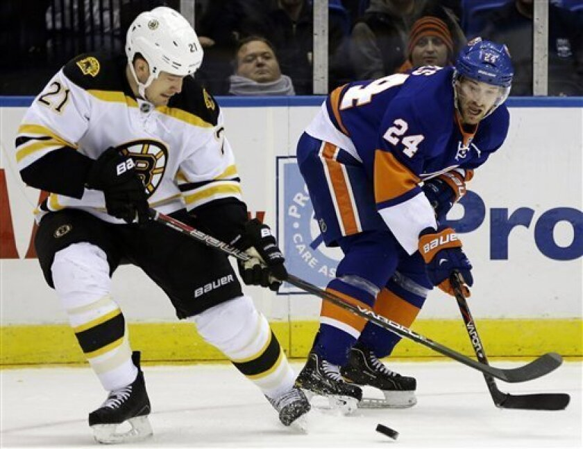 Boston Bruins defenseman Andrew Ference (21) and New York Islanders center Brad Boyes (24) compete for the puck in the second period of their NHL hockey game at Nassau Coliseum in Uniondale, N.Y., Tuesday, Feb. 26, 2013. (AP Photo/Kathy Willens)