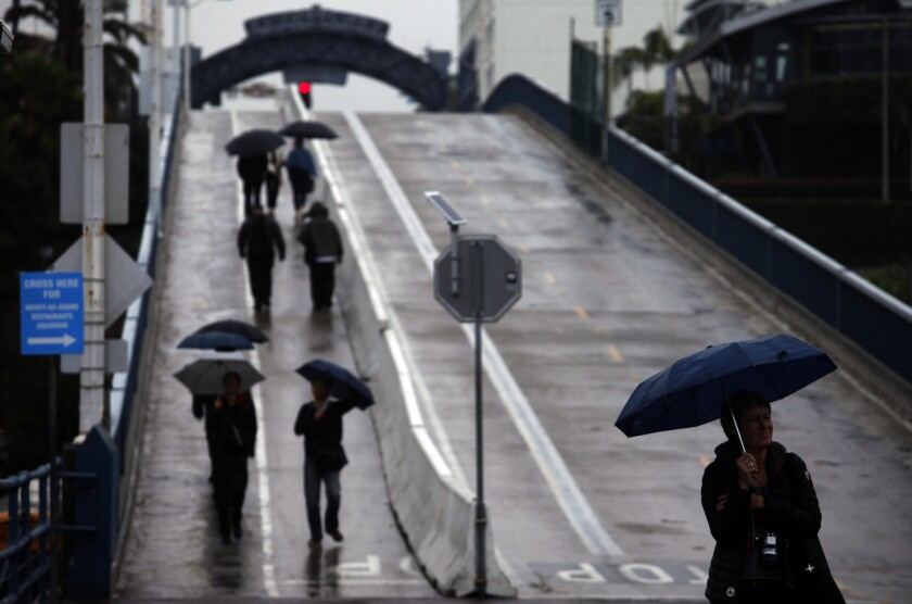 Pedestrians make their way down the ramp to the Santa Monica Pier during a recent storm.