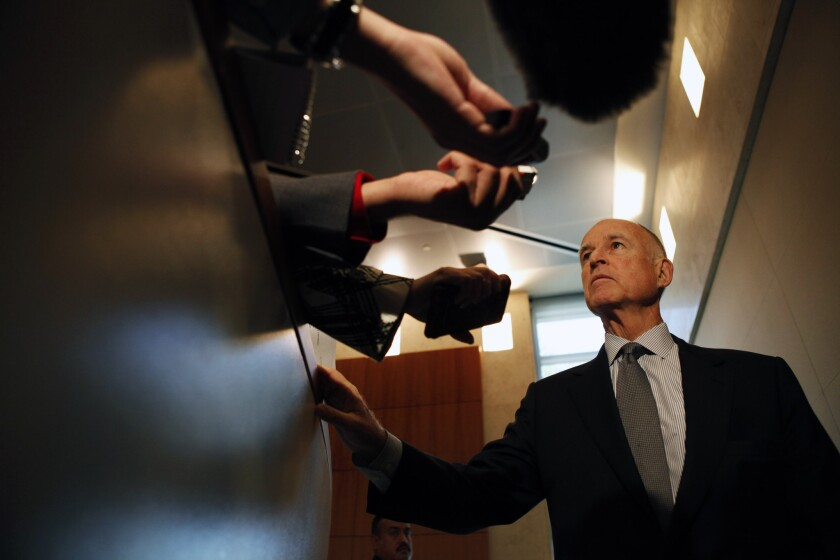 Gov. Jerry Brown talks with reporters after attending a meeting of the Cal State Board of Trustees in November.