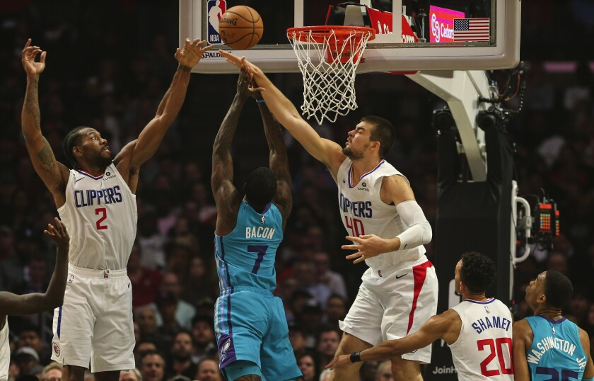 Clippers Kawhi Leonard and Ivica Zubac go for the block on Charlotte guard Dwayne Bacon.