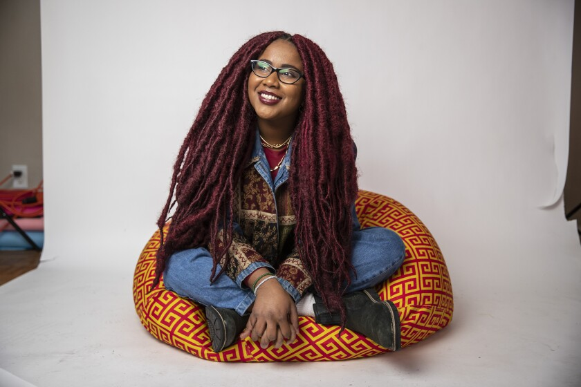 Cinematographer Sade Ndya sits cross-legged on a colorful cushion.