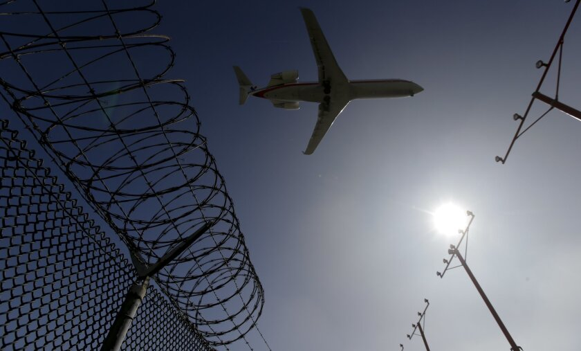 In this Friday, Feb. 6, 2015 photo, a passenger jet flies over the perimeter fence at the Los Angeles International Airport as it lands. Several hundred times from 2004 to 2015, intruders have hopped fences, slipped past guardhouses, crashed their cars through gates or otherwise breached perimeter