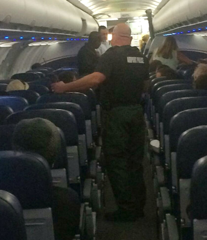 This Tuesday, Nov. 3, 2015, photo provided by Bill McCarthy shows airport police aboard a plane after an emergency landing at Eisenhower National Airport in Wichita, Kan. The U.S. Attorney's Office says a disruptive passenger who forced the diversion of the American Airlines flight from Phoenix to