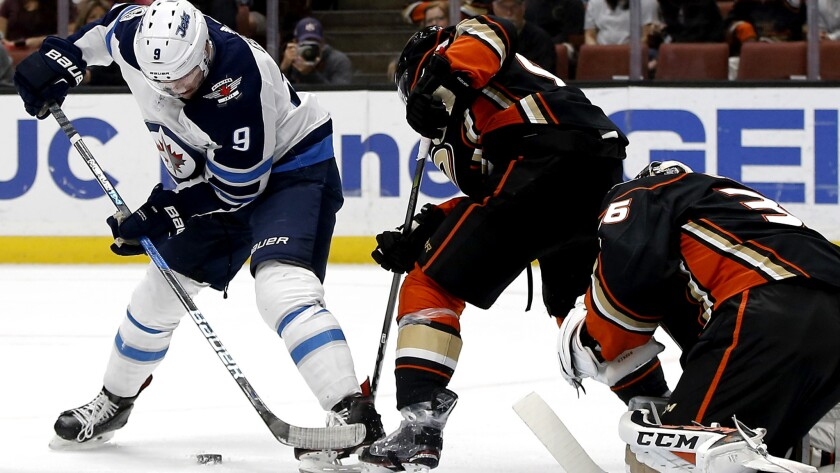 Jets center Andrew Copp (9) and Ducks defenseman Sami Vatanen battle for the puck in front of goalie John Gibson during the first period of their Nov. 24 game.