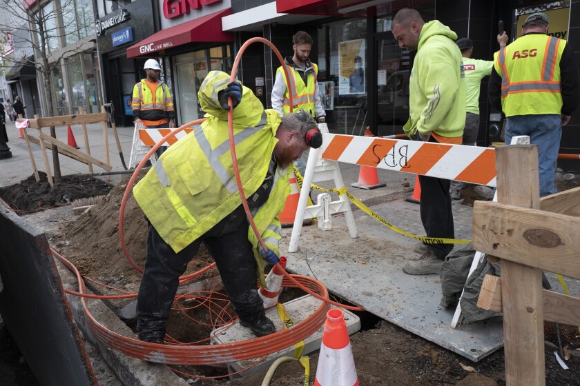Workers install conduit that will hold Verizon's fiber-optic cable, Wednesday, April 21, 2021 in New York. Wages and benefits grew quickly for U.S. workers in the first three months of the year, a sign that businesses are starting to offer higher pay to fill newly-opened jobs. U.S. workers' total compensation rose 0.9% in the January-March quarter, the largest gain in more than 13 years, the Labor Department said Friday, April 30. (AP Photo/Mark Lennihan)