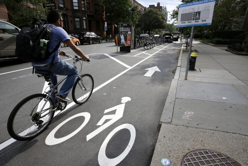 En esta foto, un cliclista va por una ciclovía entre autos estacionados y la acera en Boston. Ciudades en el mundo están reformando las ciclovías para volverlas más seguras a raíz de accidentes fatales entre bicicletas y automóviles, (AP Foto/Steven Senne)