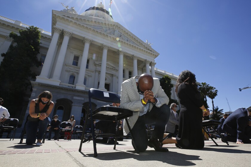 """FILE - In this June 9, 2020, file photo, Assemblyman Mike Gipson, D-Carson, bows his head as he and other members of the California Legislature kneel to honor George Floyd at the Capitol in Sacramento, Calif. Lawmakers approved, Thursday, Sept. 9, 2021, Gipson's measure that would prohibit police from using techniques that create a substantial risk of what's known as """"positional asphyxia."""" (AP Photo/Rich Pedroncelli, File)"""