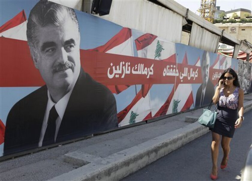 """A Lebanese woman passes a portrait of slain Lebanese Prime Minister Rafik Hariri near his grave, in downtown Beirut, Lebanon, Thursday June 30, 2011. A U.N.-backed court investigating the 2005 assassination of former Prime Minister Rafik Hariri delivered an indictment and four arrest warrants Thursday, the latest turn in a case that has transformed this Arab nation and brought down the government earlier this year. The names of the accused were not released, but the court has been expected to accuse members of the Iran-backed militant group Hezbollah. The Arabic words next to the portrait read:""""Because of what we have achieved, because of you we are going down (protest)"""". (AP Photo/Bilal Hussein)"""