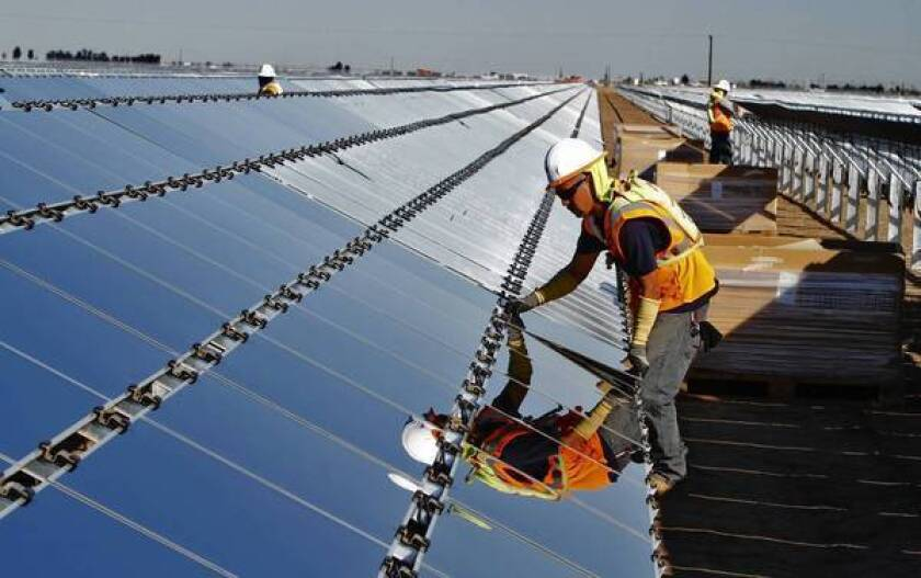 A worker installs a photovoltaic panel at the Tenaska Imperial Solar Energy South project in the Imperial Valley west of El Centro, Calif.