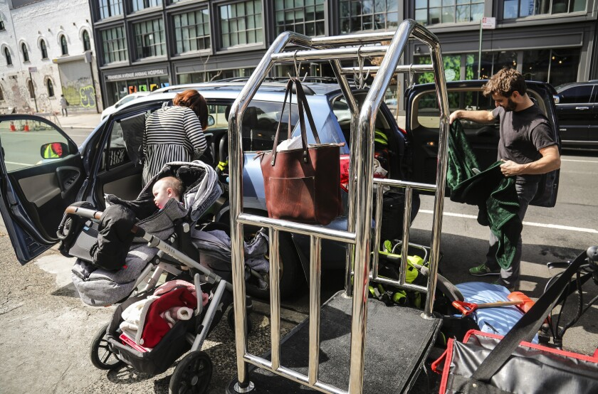 """Cailin Sandvig, left, and Justin Bracken, load their family car as they prepare to leave their home in the Crown Heights area of Brooklyn, in New York, with their newborn twins, Milo, center, and Aurelia, 10 months, to avoid the spread of the new coronavirus, Monday, March, 16, 2020. """"We are fleeing the city,"""" said Sandvig who works remotely for her job. """"We are going to end up in Wheaton, Illinois, where we have a big, old house to be in with my mom that's otherwise empty."""" (AP Photo/Bebeto Matthews)"""