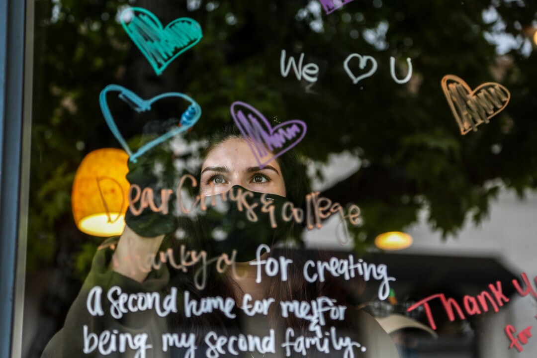A Starbucks employee in Covina writes inspiring messages on the store window during the COVID-19 pandemic.