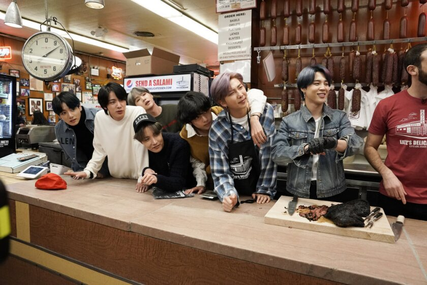 """The members of BTS — from left, Jungkook, Jin, SUGA (behind), J-Hope (front), V, RM, and Jimin — inside New York's Katz Deli on """"The Tonight Show Starring Jimmy Fallon."""""""