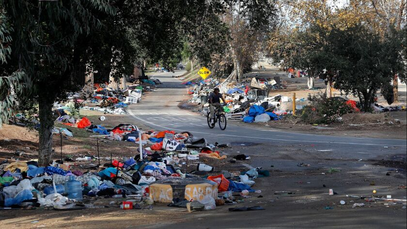 A bicyclist rides past trash piles from the Santa Ana River homeless camp after it was cleared and more than 700 people relocated in Anaheim in February.