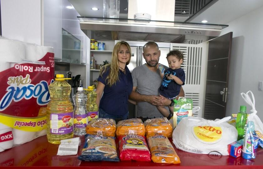 Tebie González posa para un retrato junto con su marido Ramiro Ramírez y su hijo de dos años Sebastián con la comida y los bienes básicos que compraron en la víspera en Colombia, en su casa de San Cristóbal del Táchira, Venezuela. (AP Foto/Ariana Cubillos)