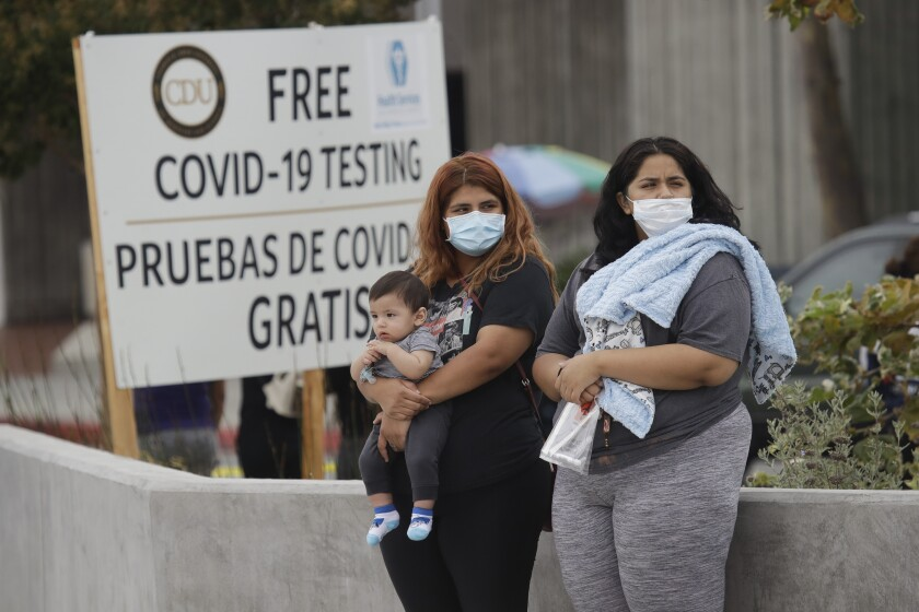 FILE - In this July 22, 2020, file photo, two women and a child wait to take a coronavirus test at a mobile testing site at the Charles Drew University of Medicine and Science in Los Angeles. California's plan to safely reopen its economy will begin to require counties to bring down coronavirus infection rates in disadvantaged communities that have been harder hit by the pandemic. (AP Photo/Marcio Jose Sanchez, File)