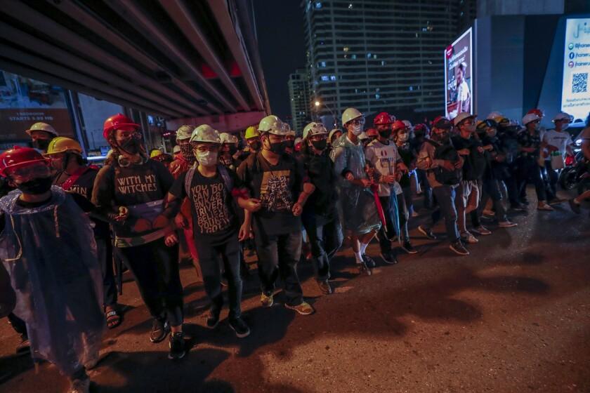 Activistas prodemocracia crean una cadena humana ante las barricadas policiales durante su marcha hacia la Casa de Gobierno, la oficina del primer ministro, durante una protesta en Bangkok, Tailandia, el miércoles 21 de octubre de 2020. (AP Foto/Sakchai Lalit)