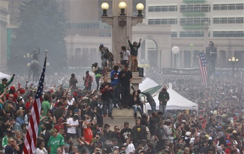 Members of a crowd numbering tens of thousands smoke marijuana and listen to live music, at the Denver 420 pro-marijuana rally at Civic Center Park in Denver on Saturday, April 20, 2013. Even before the passage in November 2012 of Colorado Amendment 64 promised the legalization of marijuana for rec