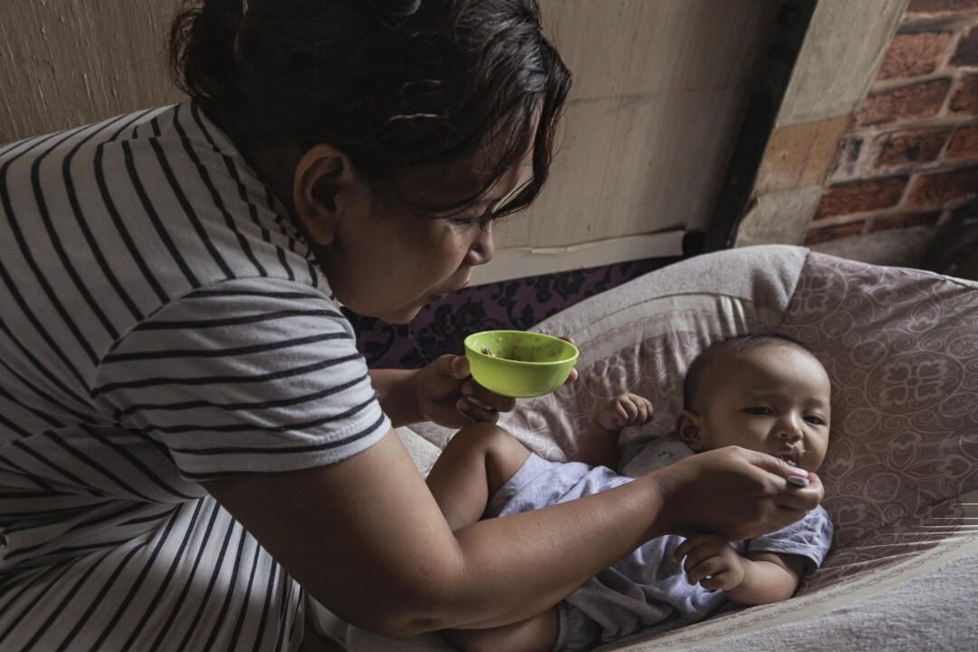 A woman holding a green bowl feeds an infant
