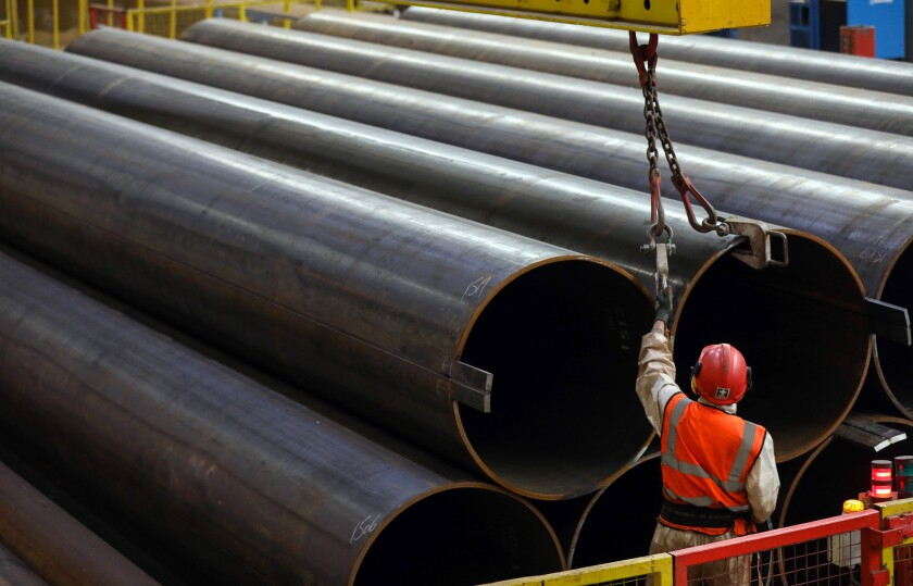 An employee secures steel pipes before moving them with a crane at the SAW Pipe Mills, operated by Liberty Commodities, in Hartlepool, U.K., on Thursday. Steel and aluminum tariffs imposed by the U.S. in March may already be filtering through to prices charged by American producers of the metals.