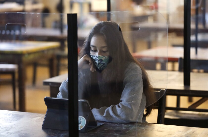 A high school student wears a mask and sits at a desk behind plexiglass.