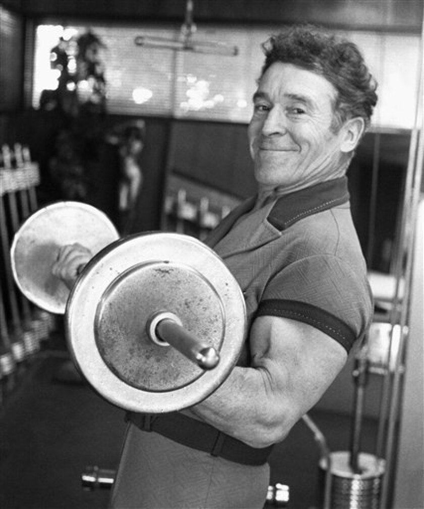 FILE - In this Feb. 20, 1980 file photo, Jack LaLanne pumps iron in the gym in his home in Hollywood, Calif. LaLanne, the fitness guru who inspired television viewers to trim down and pump iron for decades before exercise became a national obsession, has died. He was 96. (AP Photo, File)