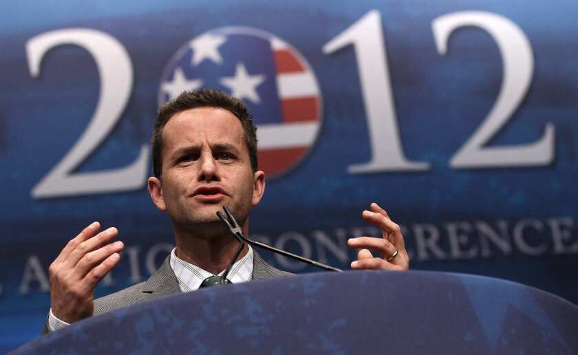 "Kirk Cameron speaks at a lectern in front of a sign saying ""2012."""