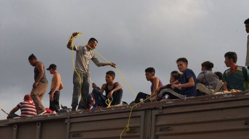Carlos Onan Galo Perez (with a yellow rope) and members of his family atop a freight train that migrants call La Bestia (the Beast). The train travels through Mexico toward the U.S.