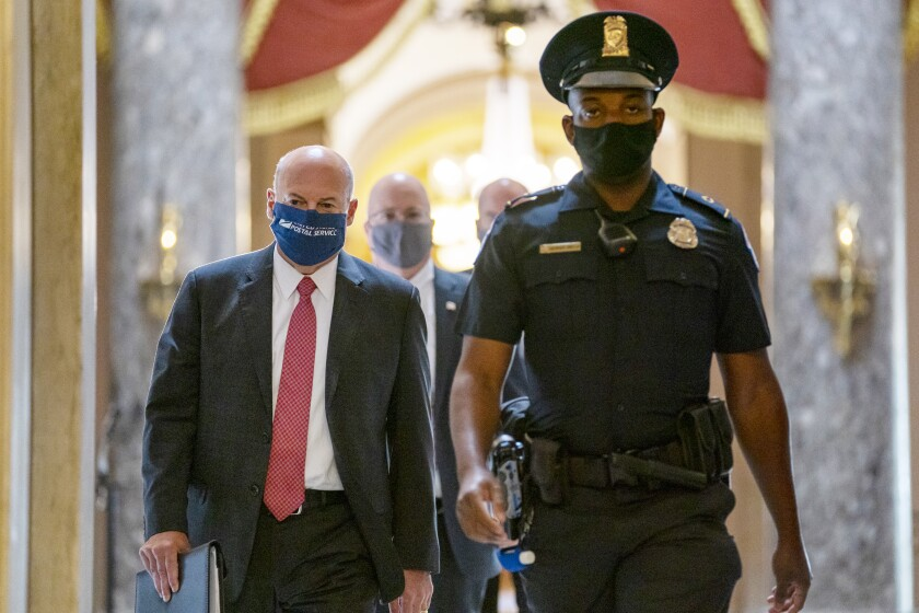 In this file photo Postmaster General Louis DeJoy, left, is escorted on Capitol Hill in Washington.