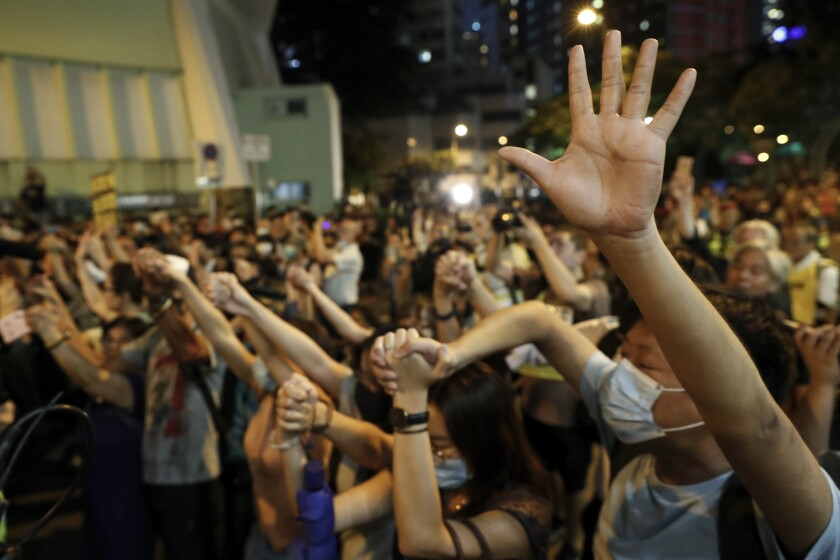 Protesters form a human chain outside the Queen Elizabeth Stadium in Hong Kong, Thursday, Sept. 26, 2019. Riot police on Thursday begun securing a stadium in downtown Hong Kong ahead of a town hall session by embattled city leader Carrie Lam, aimed at cooling down months of protests for greater democracy in the semi-autonomous Chinese territory. (AP Photo/Vincent Thian)