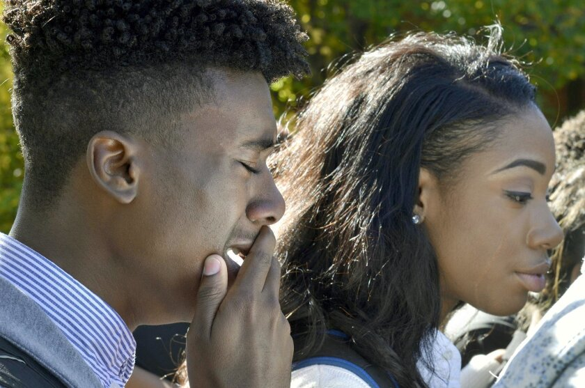 In this Saturday, Nov. 7, 2015, photo, members of the University of Missouri's Legion of Black Collegians and the Concerned Student 1950 supporters react after an on-campus protest, in Columbia, Mo. Some campus groups have been protesting the way university president Tim Wolfe has dealt with issues