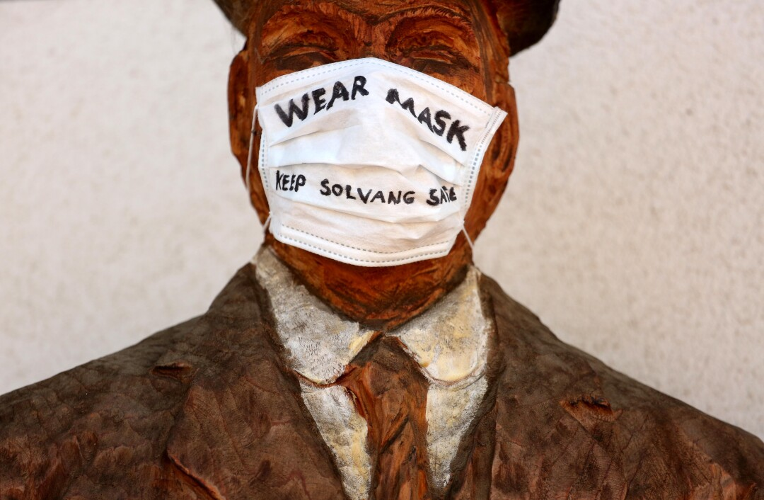 "A wooden sculpture of one of the founders of Solvang wears a surgical mask with the message, ""Wear Mask - Keep Solvang Safe,"" in front of the Copenhagen House in the California town."