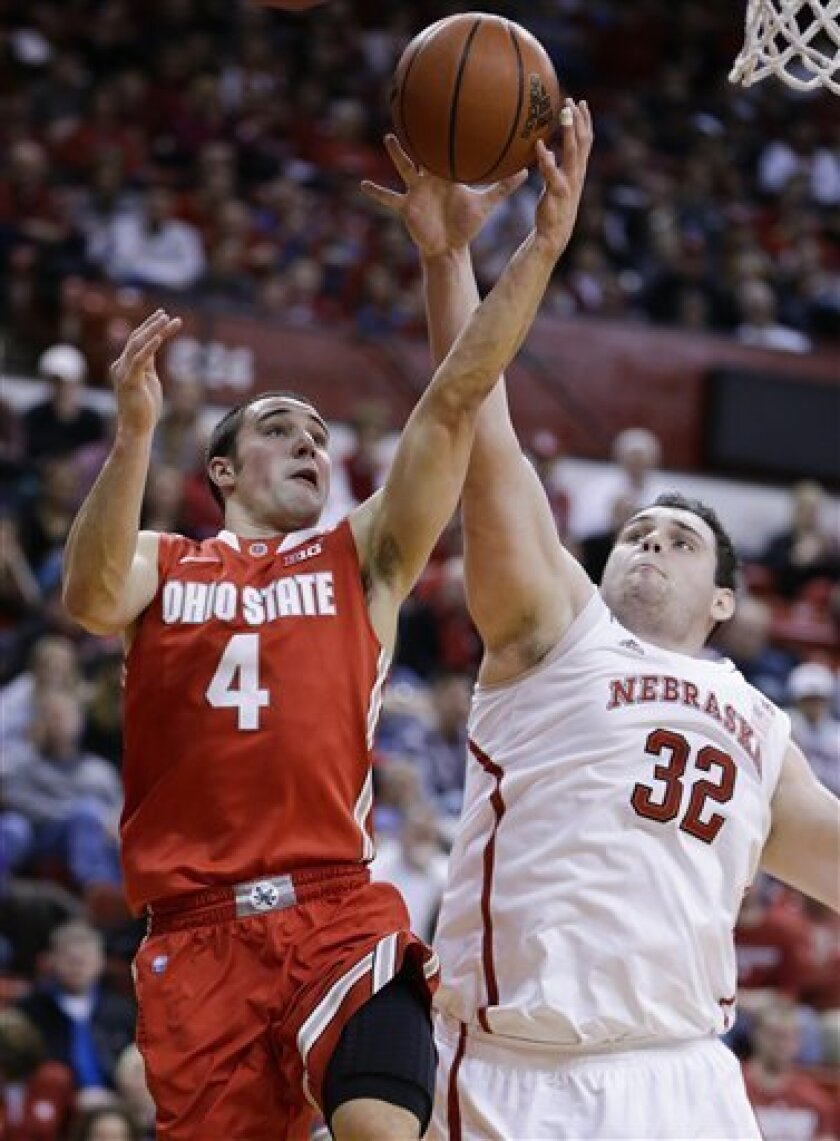 Ohio State's Aaron Craft (4) goes for a layup against Nebraska's Andre Almeida (32) in the first half of an NCAA college basketball game in Lincoln, Neb., Saturday, Feb. 2, 2013. (AP Photo/Nati Harnik)